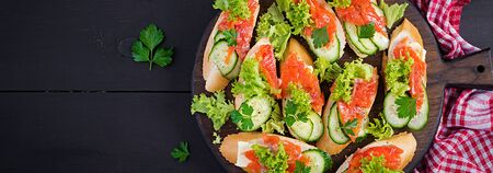 Tapas.  Salted Salmon, butter and cucumber toast sandwiches on wooden board. Banner. Top view 写真素材