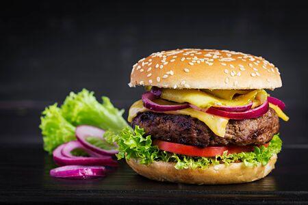 Großes Sandwich - Hamburgerburger mit Rindfleisch, Tomate, Käse, in Essig eingelegter Gurke und roter Zwiebel.