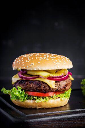Duża kanapka - hamburger burger z wołowiną, pomidorem, serem, ogórkiem kiszonym i czerwoną cebulą.
