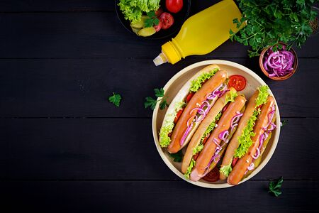 Hot dog with  sausage, pickled cucumber, tomatoes, red onions and lettuce on dark wooden background. Summer hotdog. Top view Stock Photo