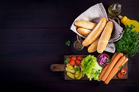 Ingredients for hot dog with  sausage, pickled cucumber, tomatoes, red onions and lettuce on dark wooden background. Summer hotdog. Top view