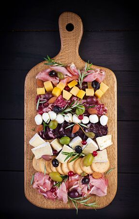 Antipasto platter with ham, prosciutto, salami, cheese, crackers and olives on a wooden background. Christmas table. Top view, overhead Stock Photo