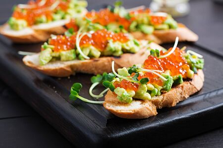 Sandwiches with salmon red caviar and salsa with avocado. Sandwich for lunch. Delicious food.