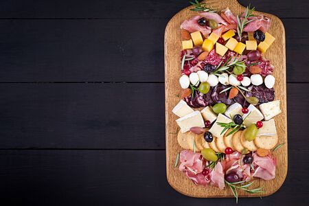Antipasto platter with ham, prosciutto, salami, cheese,  crackers and olives on a wooden background.  Christmas table. Top view, overhead