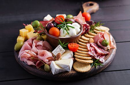 Antipasto platter with ham, prosciutto, salami, cheese,  crackers and olives on a wooden background.  Christmas table.