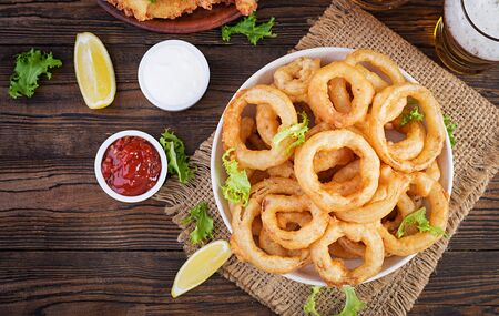 Onion rings in batter with sauce and cheese sticks. Beer snacks. Top view, overhead, copy space