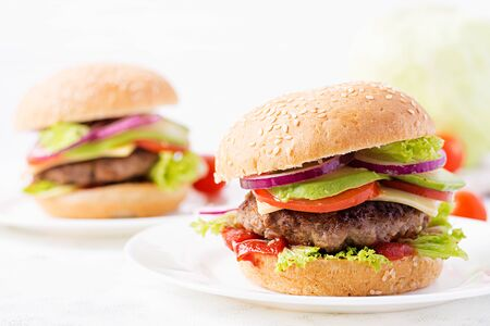 Big sandwich - hamburger burger with beef, avocado, tomato and red onions on light background. American cuisine. Fast Food Stockfoto