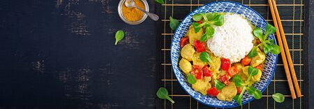 Indian chicken curry with basmati rice in blue bowl.  Traditional Indian dish. Chicken tikka masala. Indian cuisine. Top view, banner Banco de Imagens