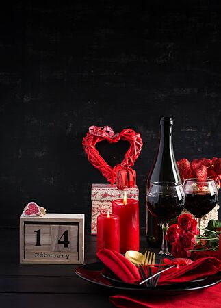 Valentines day dinner with table setting with gift, red roses, hearts with two wineglasses on dark background.