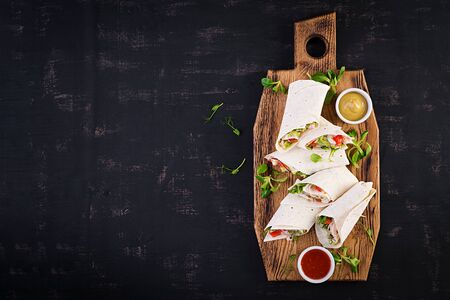 Fresh tortilla wraps with chicken and fresh vegetables on wooden board. Chicken burrito. Mexican food. Healthy food concept. Mexican cuisine.Top view, overhead
