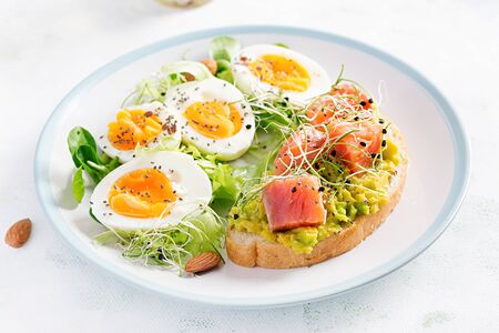 Breakfast. Healthy open sandwich on toast with avocado and salmon, boiled eggs, herbs, chia seeds on white plate with copy space. Healthy protein food.