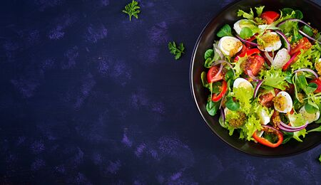 Fresh salad with vegetables tomatoes, red onions, lettuce and quail eggs. Healthy food and diet concept. Vegetarian food. Top view, overhead