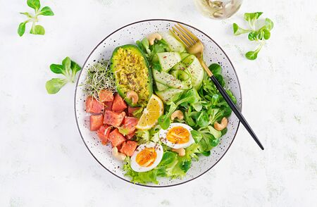 Ketogenic diet breakfast. Salt salmon salad with greens, cucumbers, eggs and avocado. Ketopaleo lunch. Top view, overhead