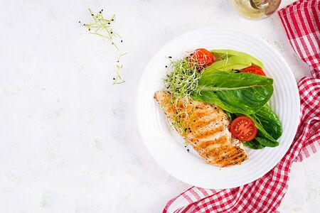 Chicken grilled fillet with salad fresh tomatoes and avocado. Healthy food, ketogenic diet, diet lunch concept. KetoPaleo diet menu. Top view, flat lay