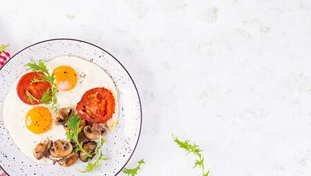 Ketogenic food. Fried egg, mushrooms and sliced tomatoes. Keto, paleo breakfast. Top view, overhead, copy space Stock Photo