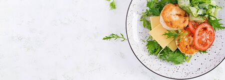 Ketogenic lunch. Chicken burger with tomato, cucumber, cheese and arugula salad without bun. Chicken patties. Healthy food. Ketopaleo diet. Top view, banner Stock Photo