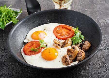 Ketogenic food. Fried egg, mushrooms and sliced tomatoes. Keto, paleo breakfast. Stock Photo