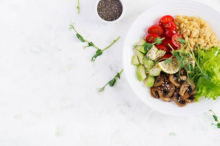 Trendy salad. Vegan Buddha bowl with lentil, avocado, mushrooms, lettuce, tomatoes and chia seeds. International Day Without Meat. Vegetarian salad. Top view, overhead, flat lay