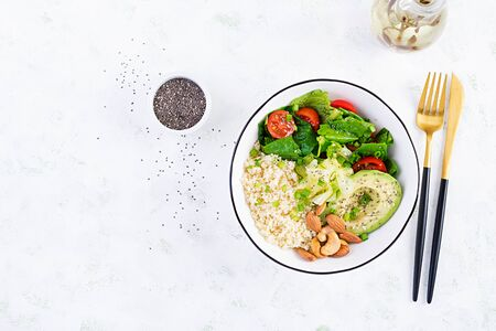 Trendy salad. Vegan Buddha bowl with bulgur, avocado, cucumber, lettuce, tomatoes and chia seeds. International Day Without Meat. Vegetarian salad. Top view, overhead, flat lay