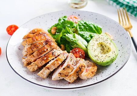 Trendy salad. Chicken grilled fillet with salad fresh tomatoes and avocado. Healthy food, ketogenic diet, diet lunch concept. KetoPaleo diet menu.