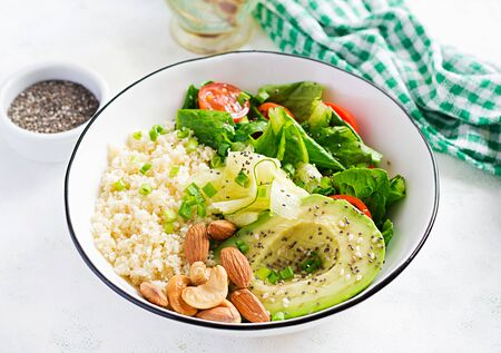 Trendy salad. Vegan Buddha bowl with bulgur, avocado, cucumber, lettuce, tomatoes and chia seeds. International Day Without Meat. Vegetarian salad.