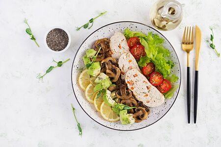 Trendy salad. Chicken meatloaf, fried mushrooms with salad fresh tomatoes and avocado. Healthy food, ketogenic diet, diet lunch concept. KetoPaleo diet menu. Top view, overhead, flat lay