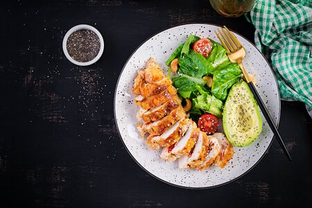 Trendy salad. Chicken grilled fillet with salad fresh tomatoes and avocado. Healthy food, ketogenic diet, diet lunch concept. KetoPaleo diet menu. Top view, overhead, flat lay 版權商用圖片