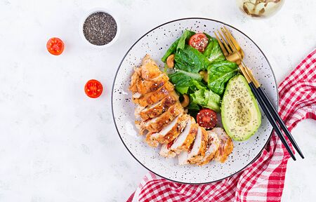 Trendy salad. Chicken grilled fillet with salad fresh tomatoes and avocado. Healthy food, ketogenic diet, diet lunch concept. KetoPaleo diet menu. Top view, overhead, flat lay Zdjęcie Seryjne