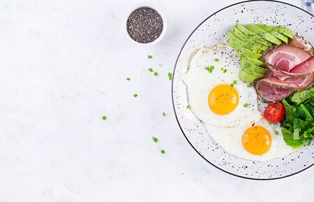 Ketogenicpaleo diet. Fried eggs, ham, avocado and fresh salad.  Keto breakfast. Brunch.  Top view, overhead