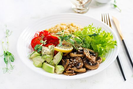 Trendy salad. Vegan Buddha bowl with lentil, avocado, mushrooms, lettuce, tomatoes and chia seeds. International Day Without Meat. Vegetarian salad.