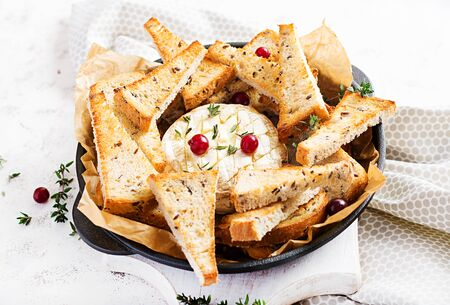 Baked camembert with toasts and thyme on light  background.