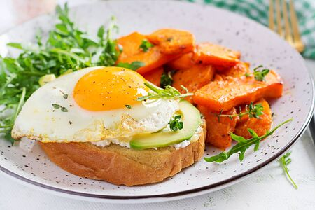Healthy breakfast. Avocado sandwich with fried egg and fried sliced pumpkin with arugula for healthy breakfast or snack. Banque d'images
