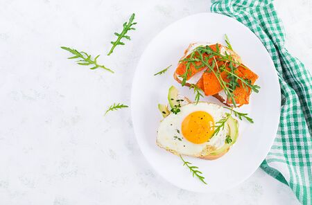 Healthy breakfast. Sandwich with avocado and fried egg, sandwich with fried sliced pumpkin for healthy breakfast or snack. Top view, overhead, flat lay