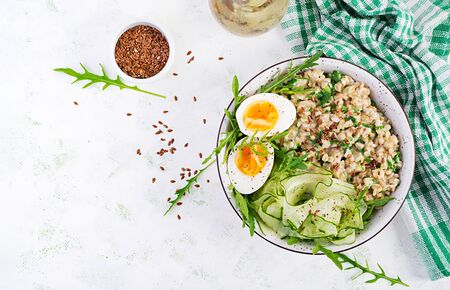 Breakfast oatmeal porridge with green herbs, boiled egg, cucumber and flax seeds. Healthy balanced food. Top view, overhead, copy space Imagens
