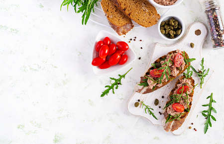 Toasts with tuna. Italian bruschetta sandwiches with canned tuna, tomatoes and capers. Top view, flat lay, copy space