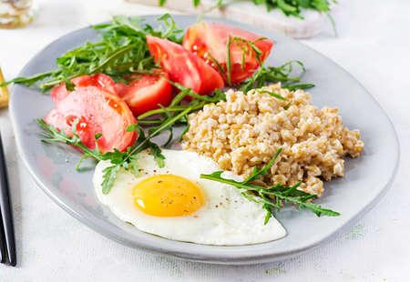 Breakfast oatmeal porridge with fried egg, tomatoes, arugula. Healthy food. Standard-Bild