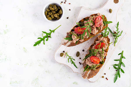 Toasts with tuna. Italian bruschetta sandwiches with canned tuna, tomatoes and capers. Top view, flat lay, copy space Foto de archivo