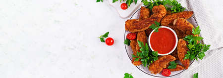 Breaded mini chicken fillets served with tomato sauce. American food. Chicken nuggets with parsley. Top view, banner, copy space