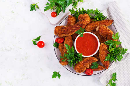 Breaded mini chicken fillets served with tomato sauce. American food. Chicken nuggets with parsley. Top view, copy space