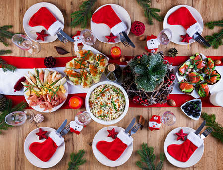 The Christmas table is served with a appetizer, decorated with bright tinsel and candles. Table setting. Christmas dinner. Flat lay. Top view Stock fotó