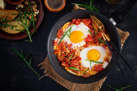 Late breakfast - fried eggs with vegetables. Shakshuka. Arabic cuisine. Kosher food. Top view