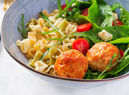 Italian pasta. Pasta with meatballs, cheese and fresh salad on light background. Dinner. Slow food concept