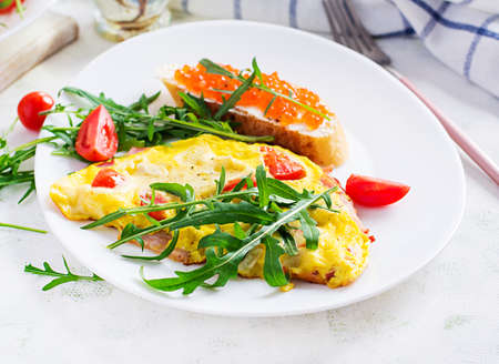 Omelette with tomatoes, cheese, ham and sandwich wich red cavier on plate. Frittata - italian omelet. 免版税图像