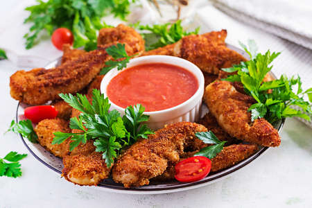 Breaded mini chicken fillets served with tomato sauce. American food. Chicken nuggets with parsley.