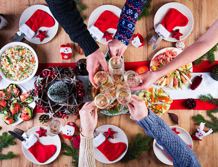 Baked turkey. Christmas dinner. The Christmas table is served with a turkey, decorated with bright tinsel and candles. Fried chicken, table. Family dinner. Top view, hands in the frame