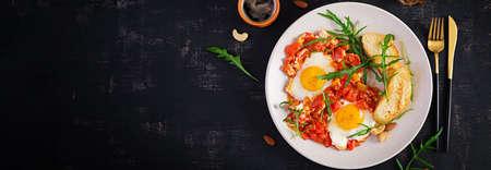 Late breakfast - fried eggs with vegetables. Shakshuka. Arabic cuisine. Kosher food. Top view, banner
