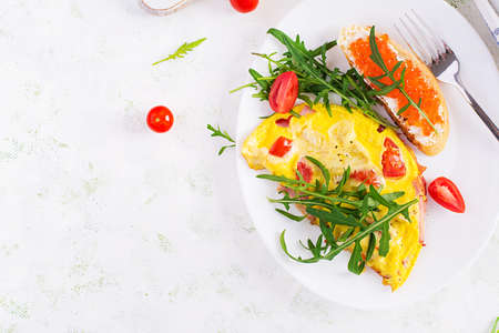 Omelette with tomatoes, cheese, ham and sandwich wich red cavier on plate. Frittata - italian omelet. Top view, overhead, copy space