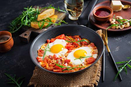 Late breakfast - fried eggs with vegetables. Shakshuka. Arabic cuisine. Kosher food. 免版税图像