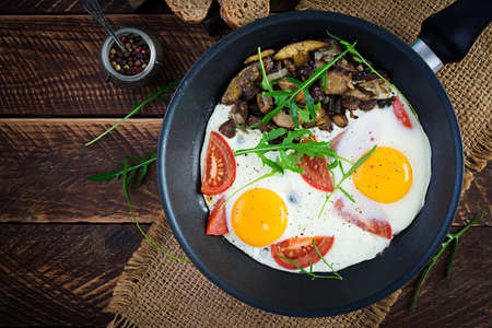Tasty breakfast - fried eggs, forest mushrooms, tomatoes and arugula. Lunch food. Top view, overhead, copy space