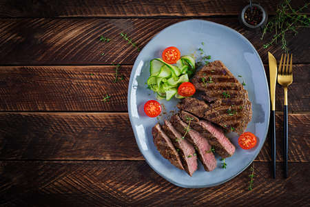 Grilled juicy steak medium rare beef with spices and fresh salad. Top view, overhead, flat lay Standard-Bild